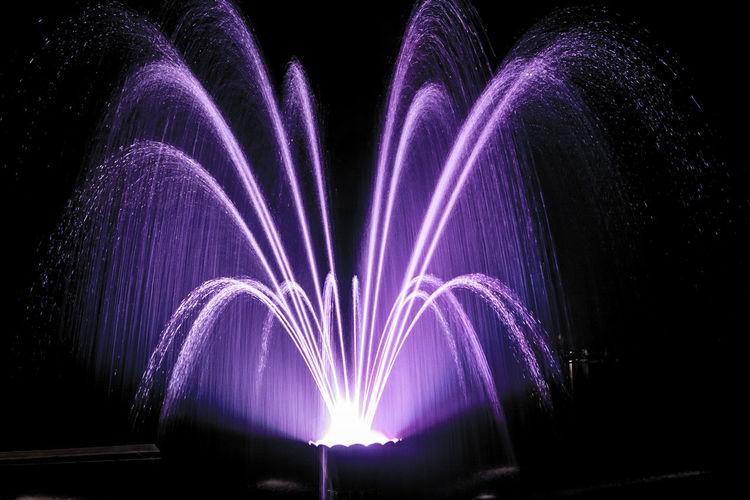 Illuminated purple fountain at night