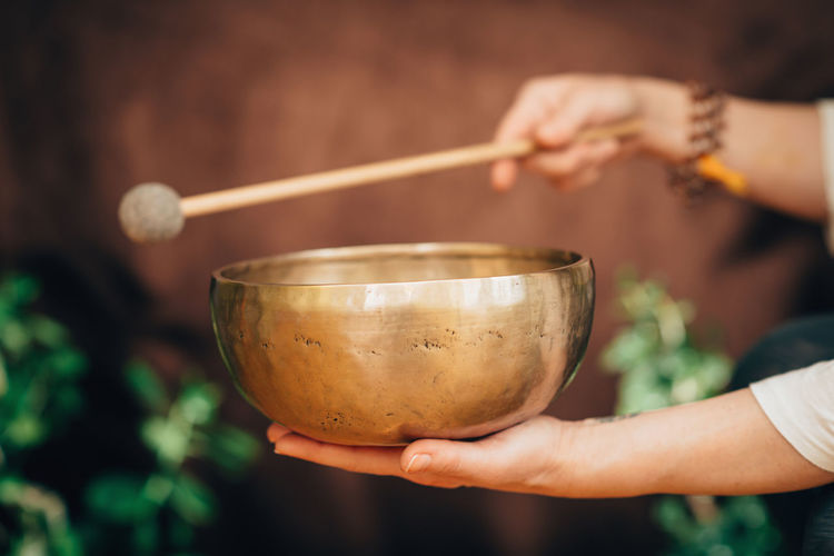 Cropped Hand Of Person Holding Bowl And Stick
