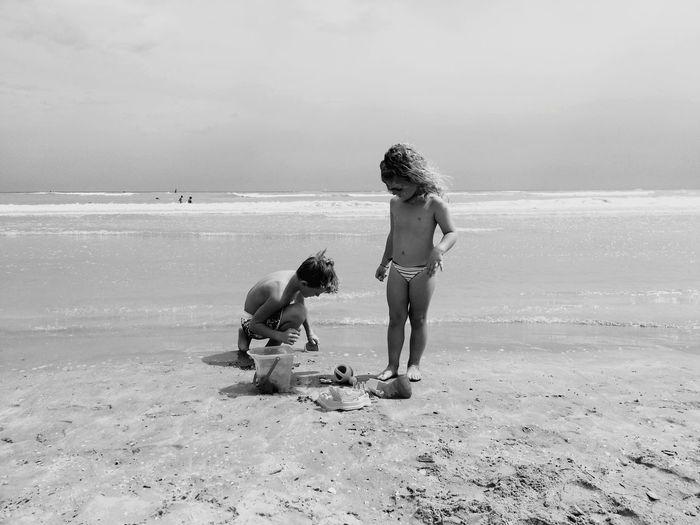 Full length of friends on beach against sea