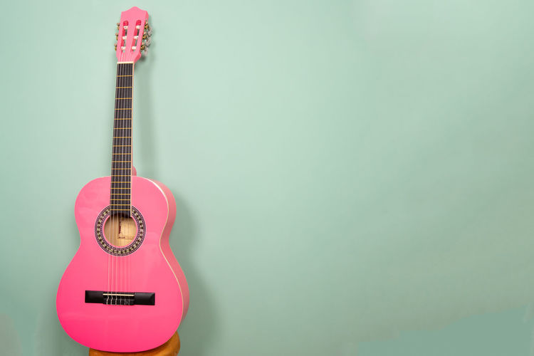 guitar in front of an empty green wall Music String Instrument Musical Instrument Guitar Colored Background Indoors  Studio Shot Musical Equipment Copy Space No People Single Object Green Background Creativity Wood - Material String Backgrounds Space Space For Text Pink Color Concept