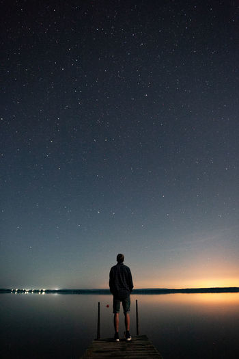 Rear view of man standing on pier over sea against sky at night