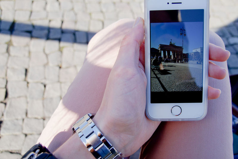 Midsection of woman holding smart phone with brandenburg gate photograph
