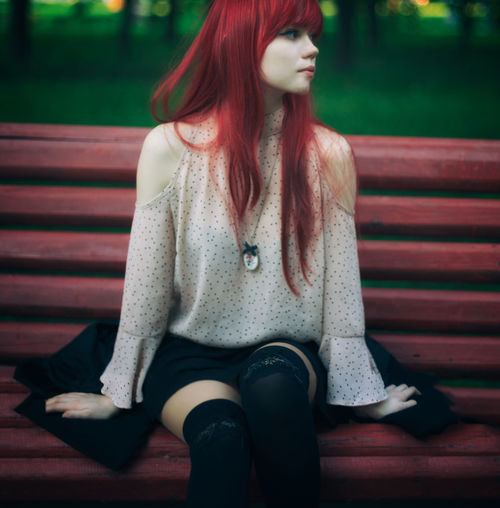 Beautiful young woman sitting in park