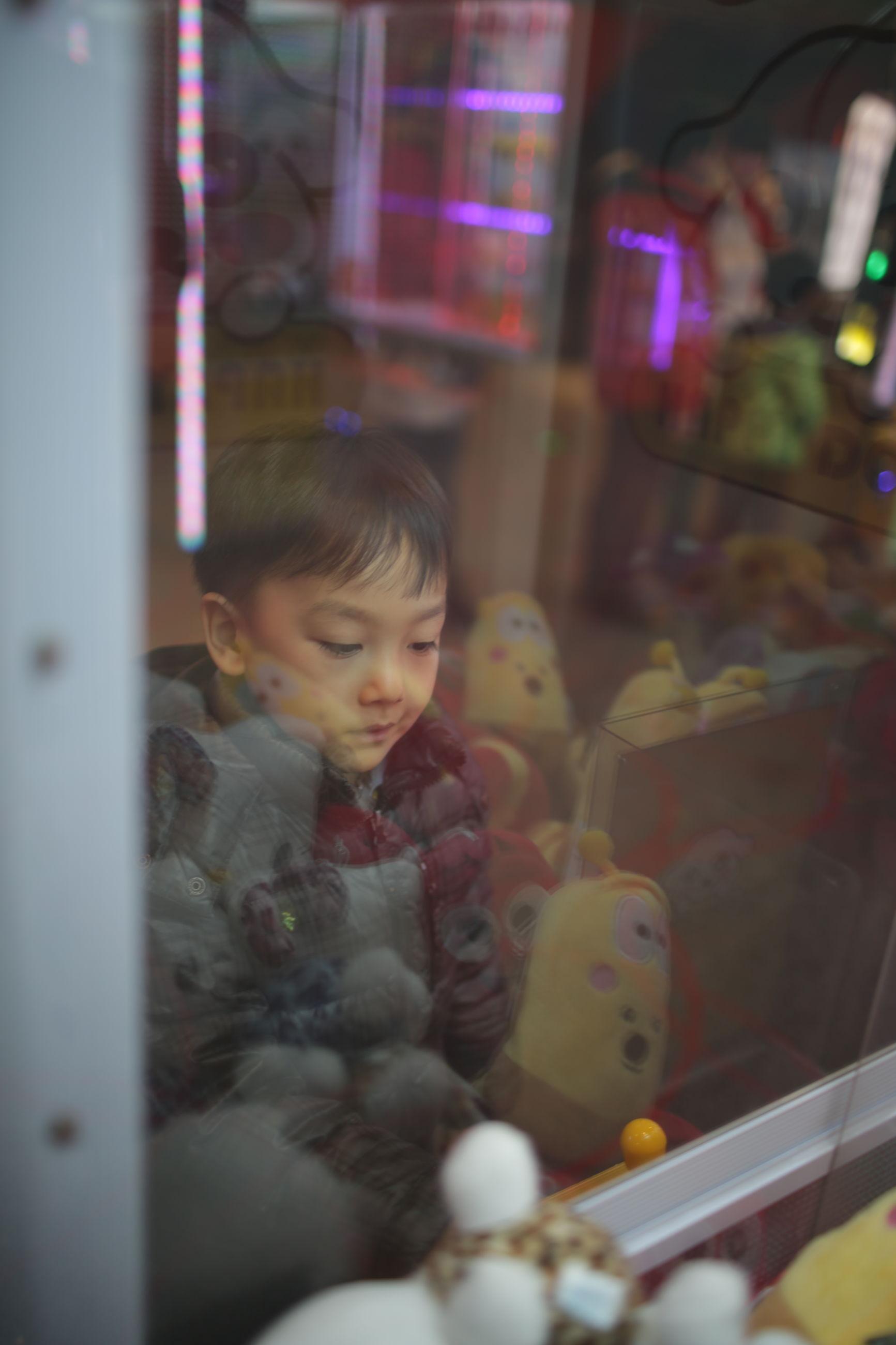 indoors, childhood, lifestyles, leisure activity, toy, person, selective focus, sitting, looking at camera, portrait, elementary age, cute, home interior, front view, focus on foreground, fun, reflection, playing