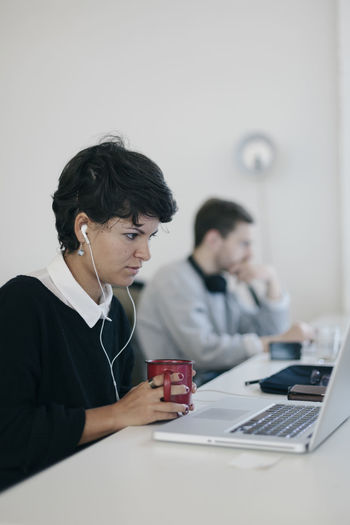 Businesswoman working in office with male colleague in background
