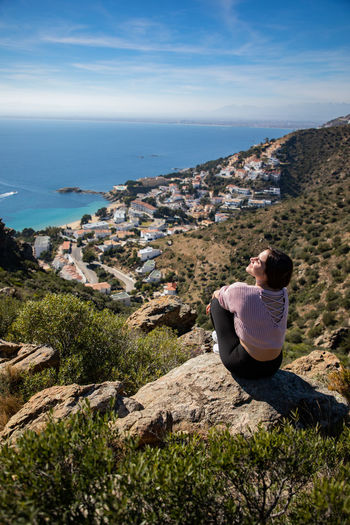 Woman sitting on rock against townscape and sea