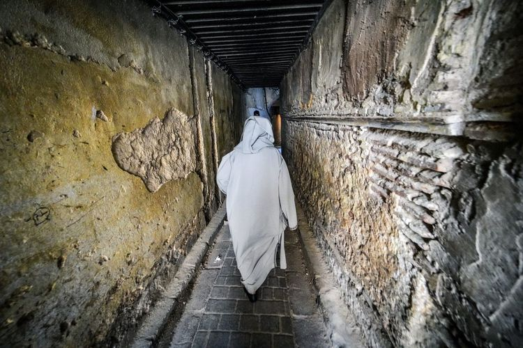 Following random people down dark alleys is pretty common in Fes. Fes Morocco Medina Medina De Fez Fes Morocco Ancient Architecture Wall - Building Feature Rear View Built Structure One Person Indoors  Full Length Wall Tunnel Day Walking The Way Forward Direction Clothing Stone Wall White Color