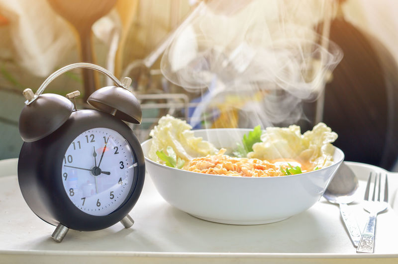 Close-up of food in bowl by alarm clock on table