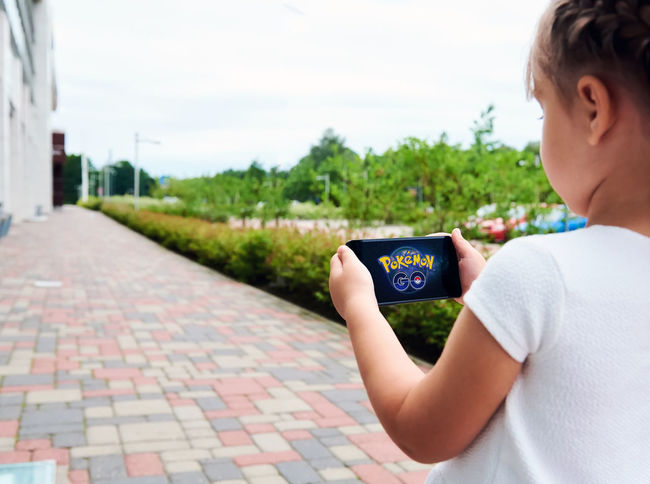 Little girl playing a Pokemon Go game outdoors. Pokemon Go is a popular virtual reality game for mobile devices. The game allows players to capture, battle, and train virtual creatures, called Pokemon, who appear on device screens as though in the real world. 5 Years Old Alone Beautiful Caucasian Cell Cellphone Child Communication Daughter Device Device Screen Entertainment Game Illustrative Internet Little Girl Mobile Phone Outdoors Phone Pokemon Go Small Girl Smartphone Summer Technology Wireless Technology