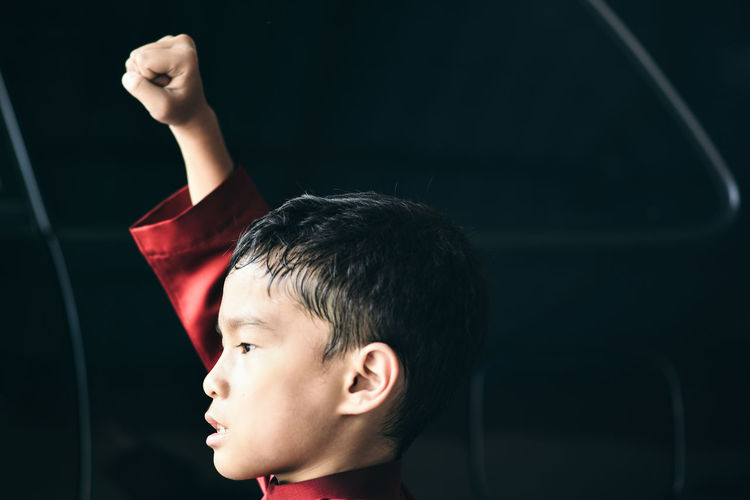 Close-Up Of Boy With Hand Raised