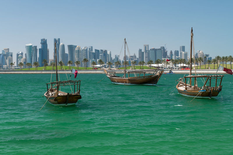 Old fisherman ships in the water in the background the West Bay of Doha, Qatar Doha West Water City Day Modern Architecture View Cityscape Downtown Bay Arabia Skyline Arabic District Capital Qatar Sea Tourism Sky Destination Skyscraper Persian Urban Development Travel Landscape Buildings Business Panorama Light Arabian Tower Rich Panoramic Qatari Boat Blue Skyscrapers Arab Gulf Economy Middle East Ships Traditional Fishing Boat Flag Dhow Nautical Vessel Urban Skyline
