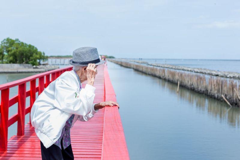 Senior man standing on pier over sea against sky