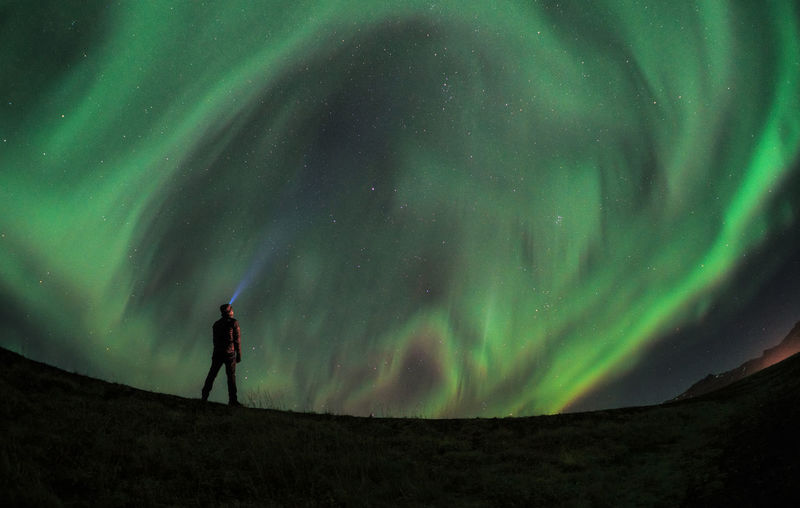 Man Standing Against Aurora Borealis On Field At Night