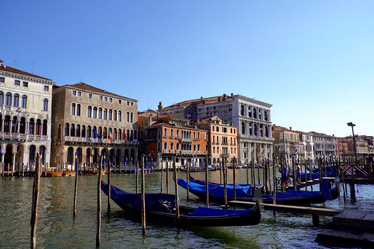 Gondolas moored in canal against buildings