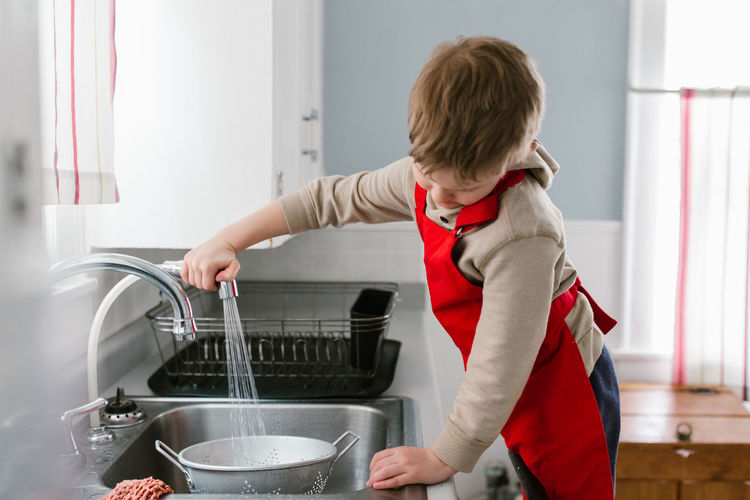 Boy filling colander in kitchen at home