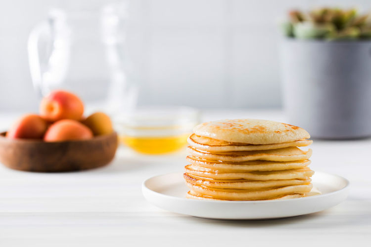 The pancakes are stacked in a plate. in the background, a bowl of honey, fruit, and a jug of milk.