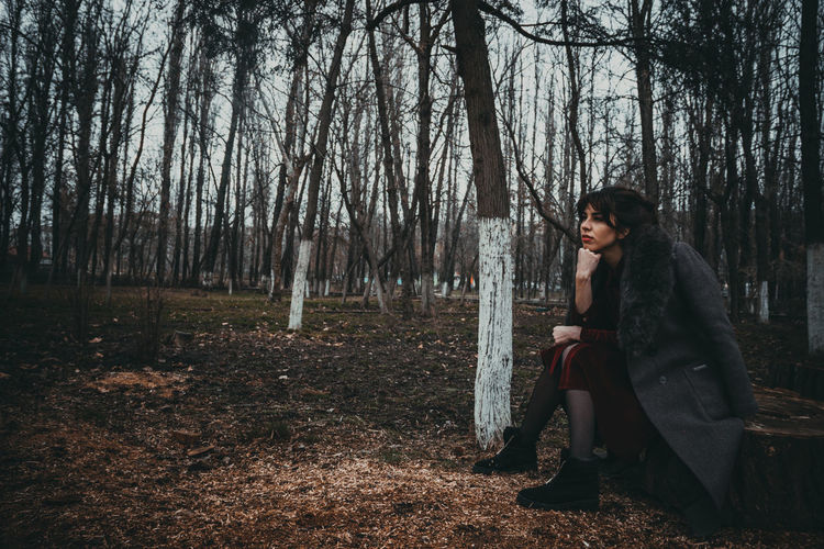 Side view of woman sitting in forest
