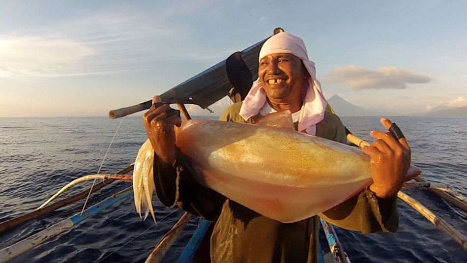 People Of The Oceans Beaming with joy with the giant diamond back squid he caught