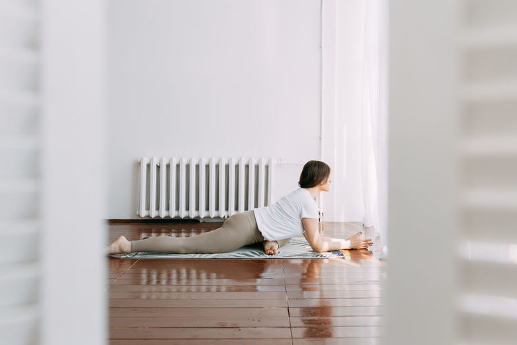 Side view of a young woman sitting on floor