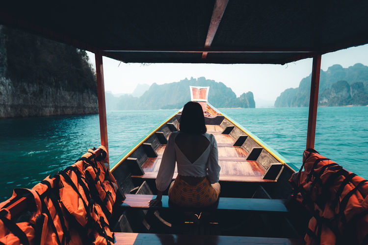 Rear view of people sitting on boat against sea