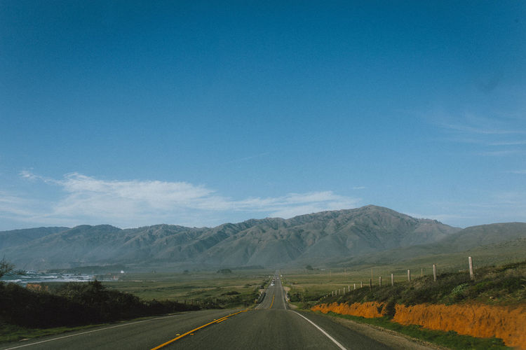 Empty road by mountains against blue sky