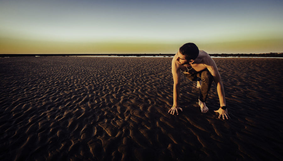 Shirtless man exercising on sand at beach against sky