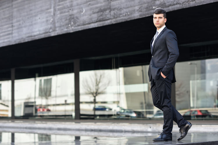 Handsome young businessman walking on footpath