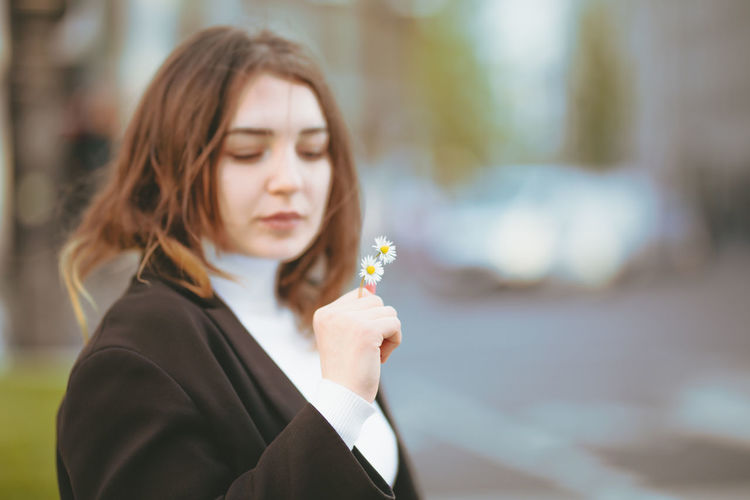 Beautiful woman holding daisies in city