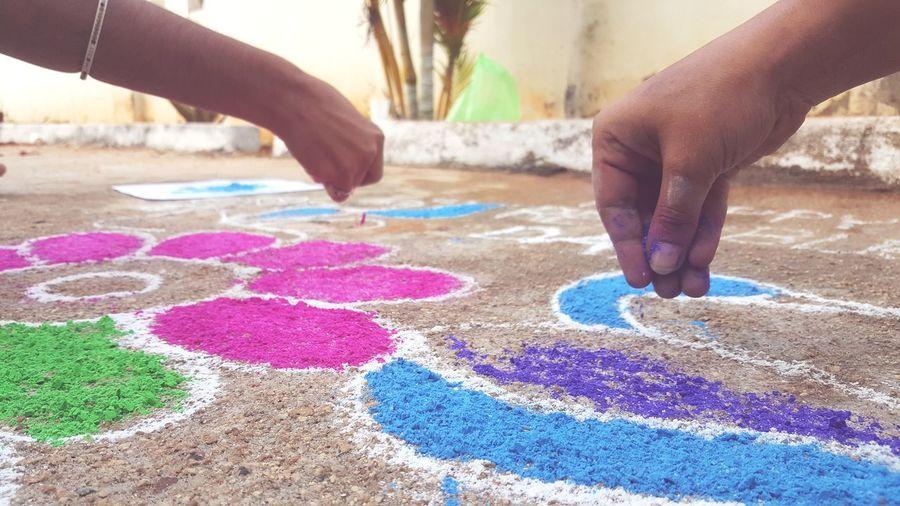 Cropped hands making rangoli on floor