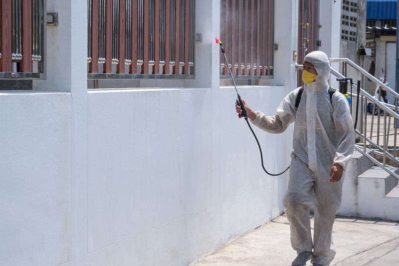 Worker praying chemical on wall in city