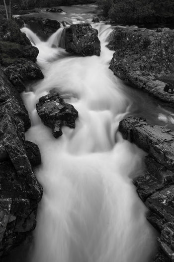Black and white scenic view of waterfall.