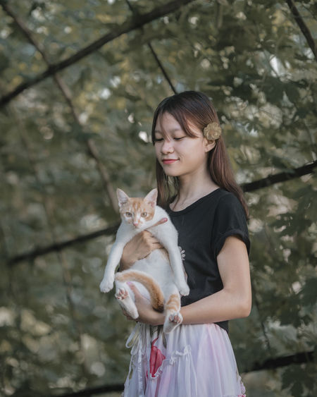Full length of woman holding pet against trees