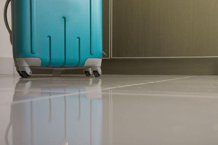 Surface level shot of turquoise wheeled luggage on tiled floor