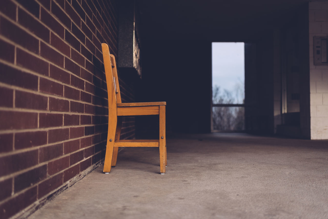 Empty Chair By Brick Wall On Floor