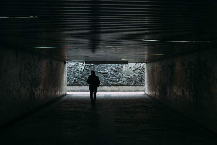 Rear view of man walking in tunnel