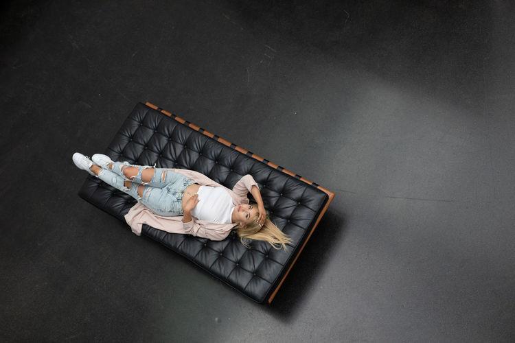 High angle portrait of woman lying on mattress