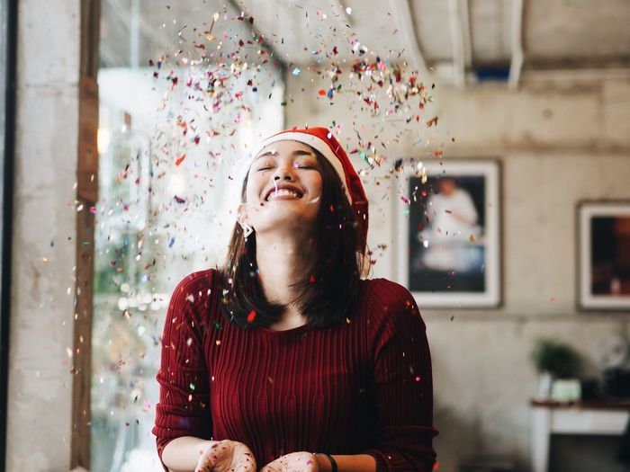 Portrait Beautiful Asian woman joyful in Christmas time. Celebration Christmas Glitter Happy Woman Cheerful Close-up Day Front View Happiness Indoors  Leisure Activity Lifestyles Looking Up One Person Real People Smiling Young Adult Young Women