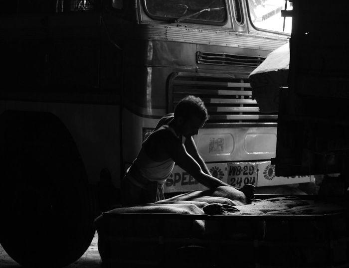 Manual Worker Arranging Sack Against Truck