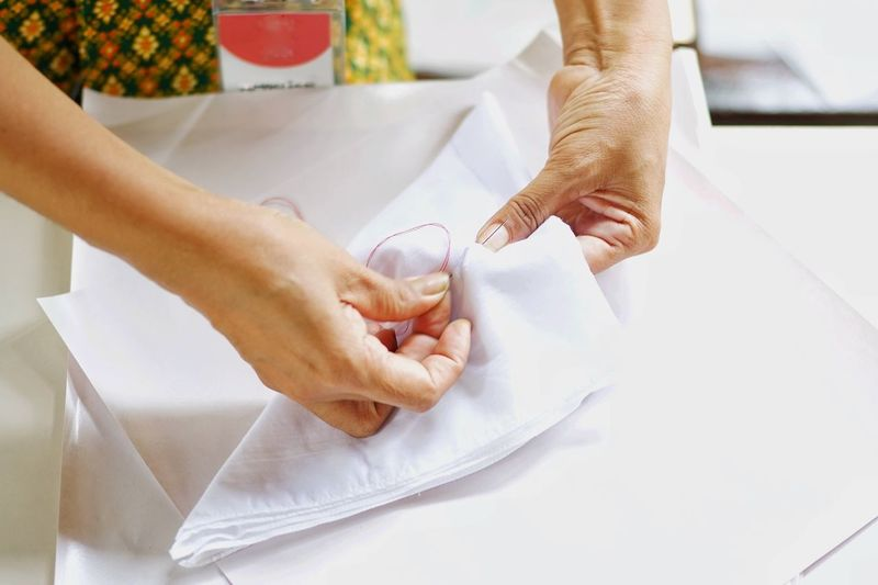 Midsection of woman sewing textile