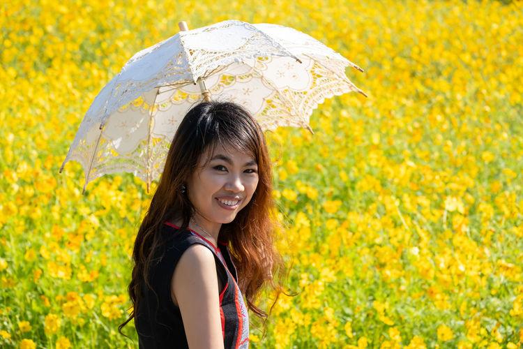 Portrait of smiling woman standing in rain during rainy season