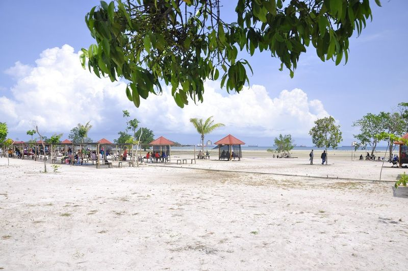 Panoramic view of people on beach against sky