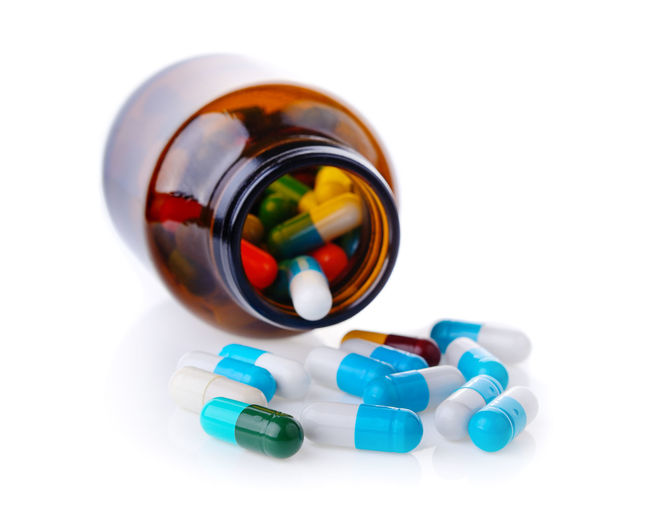 Close-up of pills with bottle on white background