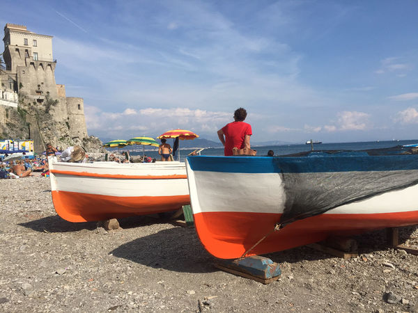 Beach Beauty In Nature Boat Building Exterior Cloud - Sky Day Longtail Boat Men Mode Of Transport Moored Nature Nautical Vessel One Person Outdoors Real People Sand Sea Sky Sunlight Transportation Water