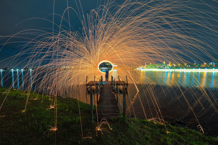Spinning burning steel wool by the lake, Putrajaya MY Blurred Motion Celebration Exploding Firework - Man Made Object Firework Display Human Body Part Illuminated Long Exposure Motion Multi Colored Night One Person Outdoors People Sky Spinning Wire Wool