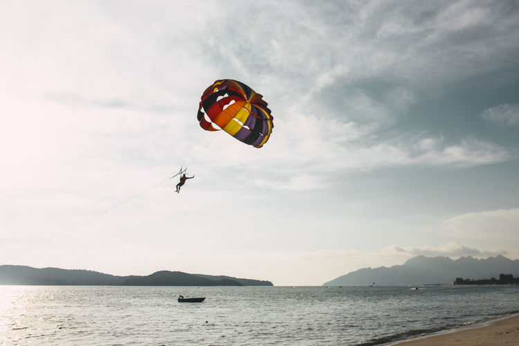 Low Angle View Of Person Paragliding Over Sea Against Sky