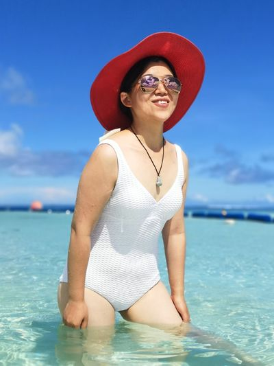 Smiling woman wearing hat while standing in sea