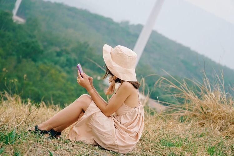 Woman sitting on grass in field