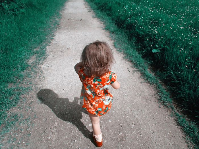 Rear view of girl walking on road