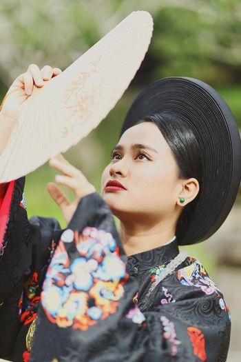 Close-up of young woman wearing traditional clothing holding hand fan
