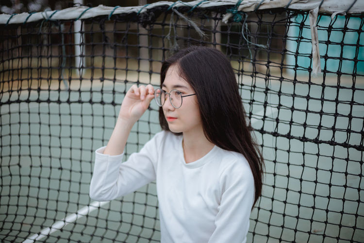 Young woman against tennis net at court
